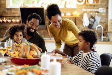 Happy African American family having fun during Thanksgiving lunch at dining table.