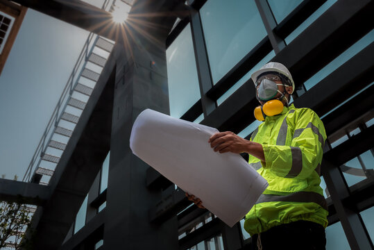 Civil Engineering people wearing face mask and safety helmet on construction site holding blueprint in his hand. Building inspector. Construction site check drawing and business workflow of building