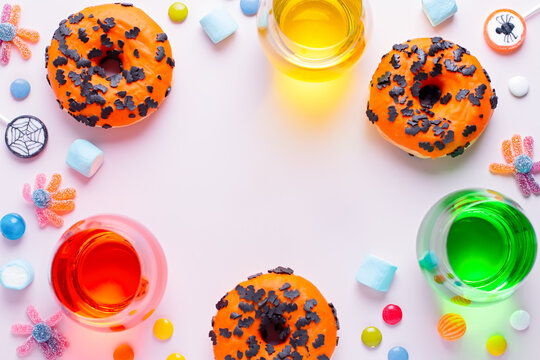 Pumpkin and chocolate donuts, colorful drinks, spider lollipops, gummy candy and marshmallows on pink - Halloween candy frame on pink table, top view, kids party concept