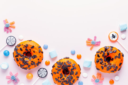 Pumpkin and chocolate donuts, spider lollipops, gummy candy and marshmallows on pink - Halloween candy border flat lay on pink table, top view, kids party concept