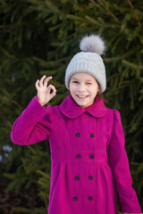 Smiling beautiful young girl in pink coat shows ok , against green of winter park.