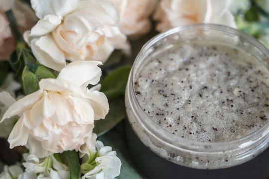 body scrub grey in a jar on a background of flowers
