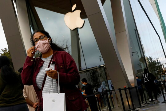 A customer exits after picking up Apple's new 5G iPhone 12 that went on sale at an Apple Store in Brooklyn, New York