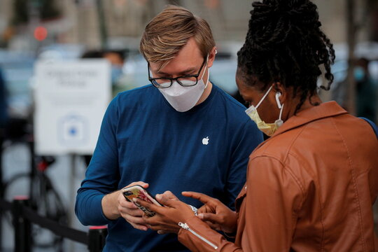 A customers speaks to an employee outside an Apple Store to pick up Apple's new 5G iPhone 12 in Brooklyn, New York