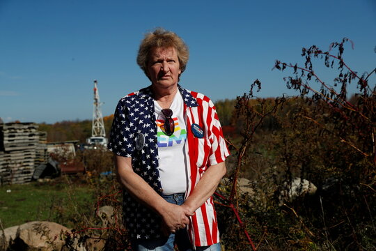 Marika Powers, a supporter of U.S. Democratic presidential candidate Joe Biden, poses near a well site which sits atop the natural gas-rich Marcellus shale formation in Western Pennsylvania outside of Union City, Pennsylvania