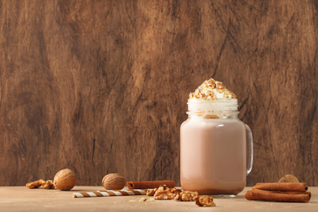 Winter hot dark chocolate or cocoa drink with whipped cream and crushed walnuts in glass jar, wooden table, copy space