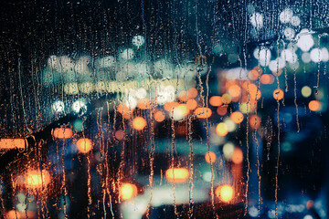 Rain drops on window with road light bokeh, City life in night in rainy season abstract background,water drop on the glass, night storm raining car driving concept. Fotomurales