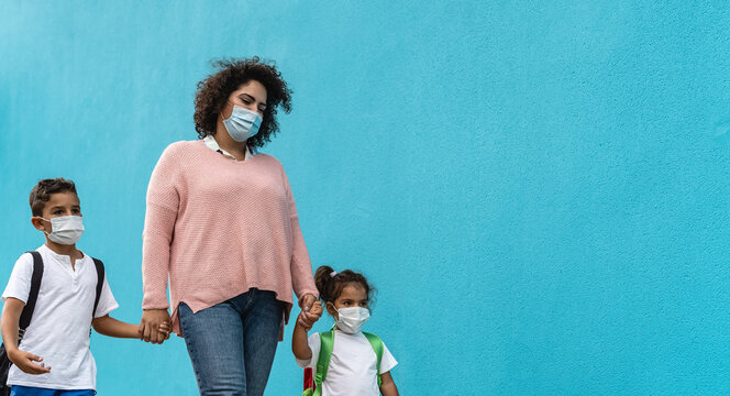 Mother with son and daughter wearing face protective mask going back to school during corona virus pandemic - Healthcare and education concept