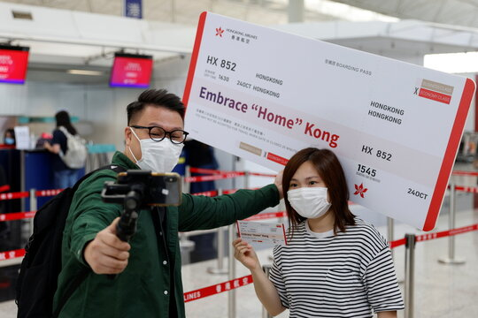 "Passengers pose for a photo before boarding Hong Kong Airline's Embrace ""Home"" Kong ""flight to nowhere"" experience, in Hong Kong"