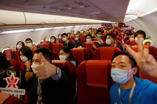 "Passengers pose for a photo as they sit on board of the Hong Kong Airline's Embrace ""Home"" Kong ""flight to nowhere"" experience, in Hong Kong"