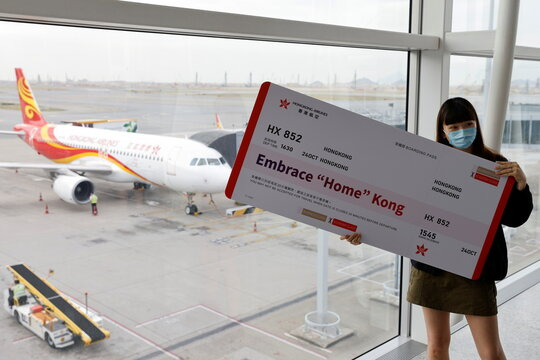 "A passenger poses for a photo before boarding Hong Kong Airline's Embrace ""Home"" Kong ""flight to nowhere"" experience, in Hong Kong"
