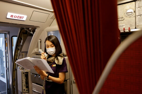 "A flight attendant speaks on the phone before take-off during Hong Kong Airline's Embrace ""Home"" Kong ""flight to nowhere"" experience, in Hong Kong"