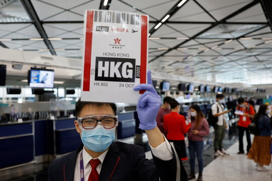 "A Hong Kong Airline's employee holds a sign before boarding Hong Kong Airline's Embrace ""Home"" Kong ""flight to nowhere"" experience, in Hong Kong"