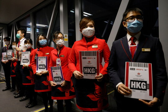 "Ground crews hold signs to greet passengers as they come back from the Hong Kong Airline's Embrace ""Home"" Kong ""flight to nowhere"" experience, in Hong Kong"