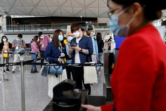 "A passenger holds a passport before boarding Hong Kong Airline's Embrace ""Home"" Kong ""flight to nowhere"" experience, in Hong Kong"