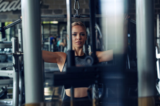Young fitness woman execute exercise with exercise-machine in gym.