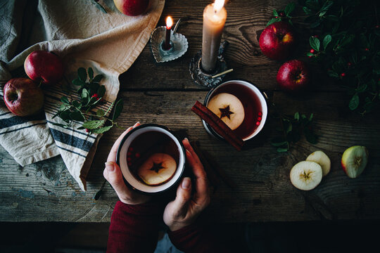 Flat lay with two metal cups with aromatic apple and cranberries tea with cinnamon stick, burning candles, apples and fir branches on old wooden table.