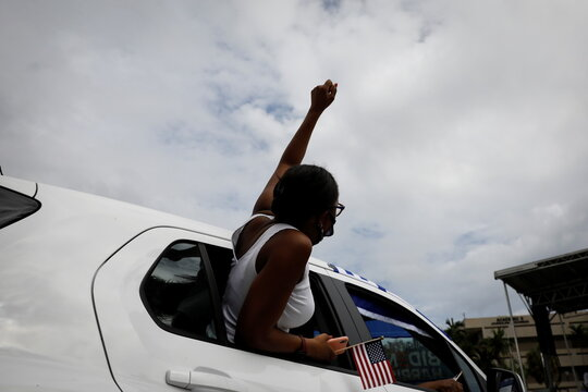 A supporter waits at a drive-in rally for former U.S. President Barack Obama in Miami