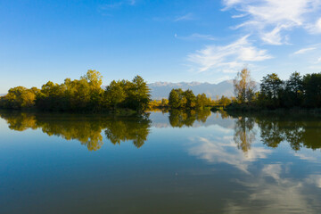 Lake at the edge of the mountains with forest reflected in the clear water. Idyllic autumn landscape. The forest and the sky in the reflection of the water. Quiet autumn fishing landscape