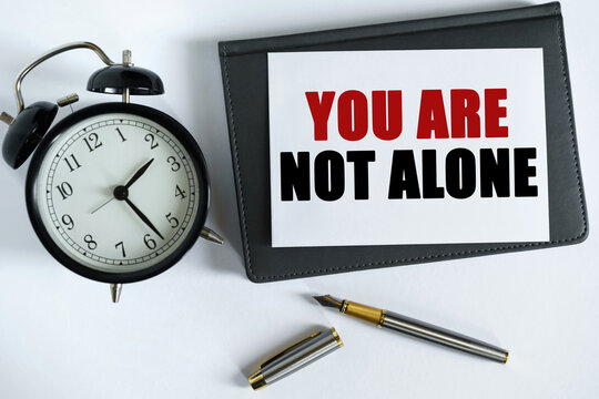 On the table there is a clock, a pen, a notebook and a card on which the text is written - YOU ARE NOT ALONE