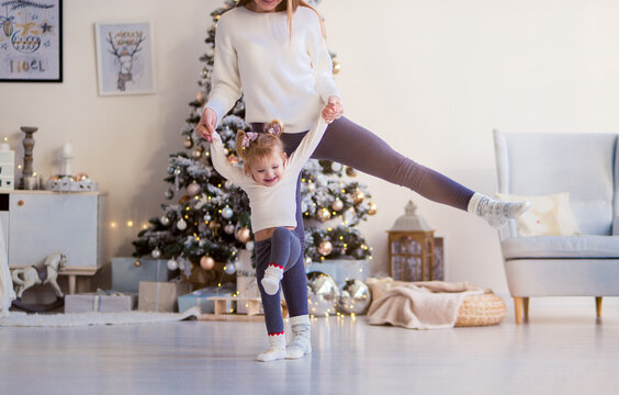 Mom holds the hands of a little daughter, she raised her leg up and side, take the first steps. girls in white sweaters, in the background a Christmas tree