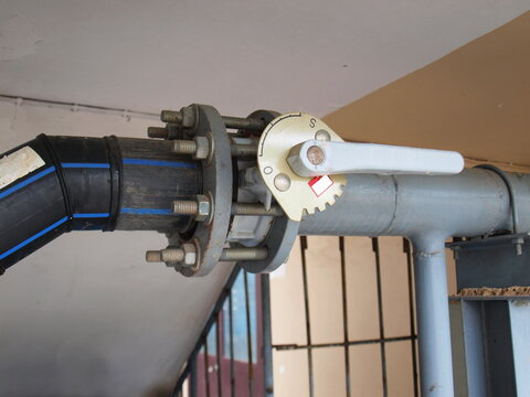 Butterfly valve with nuts and bolts. Water valve in the valve open position to control the water flow rate on the background of the concrete wall. Close focus and choose a subject