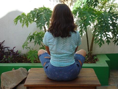 Adolescente sentada de pies cruzados, de espaldas 2