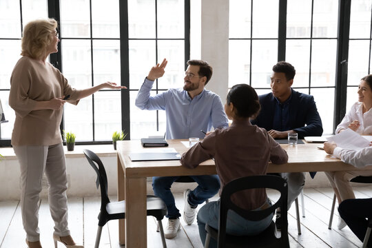 Smiling Caucasian male employee raise hand ask answer question at meeting with middle-aged businesswoman or CEO. Confident motivated man worker participate in team discussion at briefing.