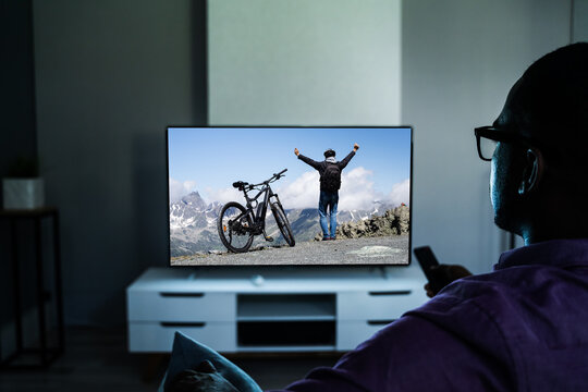 African Man Watching TV Movie In Glasses