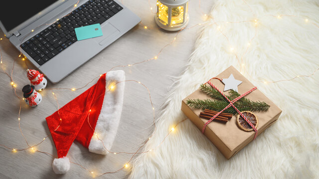 Top view of decorated gift box, laptop and credit card on floor. Cozy evening in home, xmas lights. Christmas online shopping concept. Winter holidays sales.