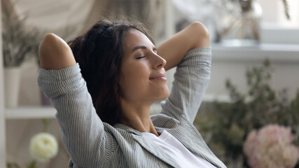 Fototapeta Close up of young Caucasian woman rest hands over head daydream or visualize relieve negative emotions. Happy calm millennial female relax with eyes close, meditate or sleep. Stress free concept. obraz