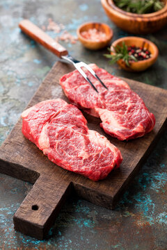 Fresh raw Chuck Roll beef steaks on a cutting wooden board, selective focus