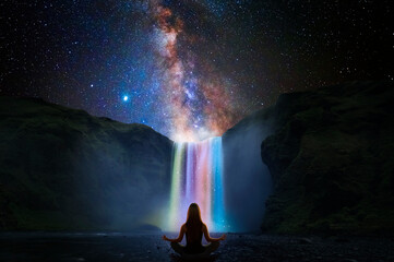 Woman doing yoga in front of a magic waterfall