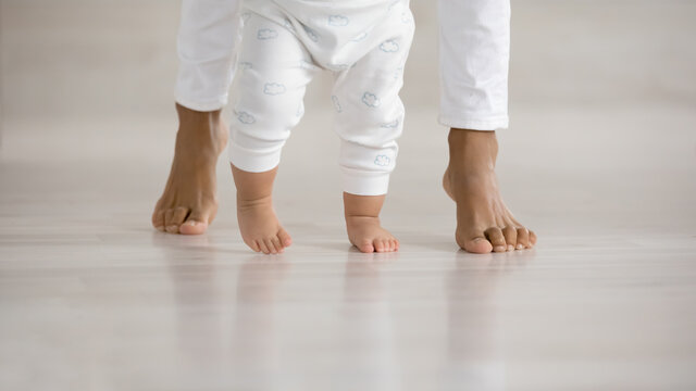 Crop close up of little baby infant learn walking at home wooden floor holding mom hands. Cute small toddler child make first steps with mom love, care and support. Childcare, motherhood concept.