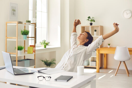 Business woman sitting at office desk, taking break from work and stretching stiff, tense muscles