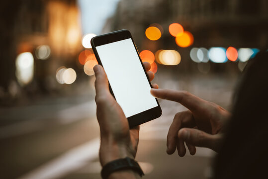 Close-up of male hands with smartphone on night street. Empty blank screen. Mock-up