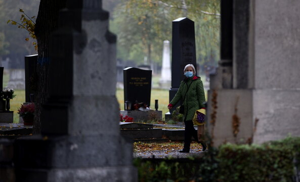 A woman wearing a protective face mask walks between tombstones at the Zentralfriedhof cemetery on an autumn day ahead of All Saints Day in Vienna