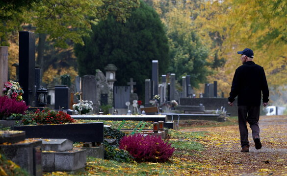 A man walks next to tombstones at the Zentralfriedhof cemetery on an autumn day ahead of All Saints Day in Vienna