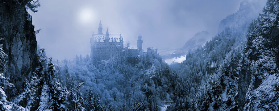 The famous Neuschwanstein Castle in the background of snowy mountains and hills in in the light of the sun through a snowstorm and blizzard. Germany, Europe