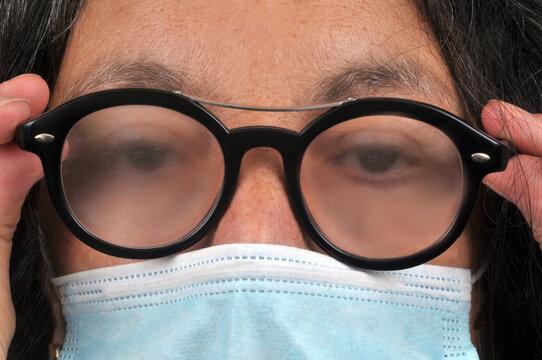 Femme portant un masque avec de la buée sur les lunettes