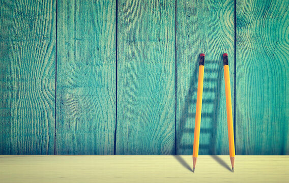 Good copywriting concept. Pencils against wooden wall forming a ladder