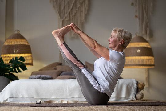 Active senior woman doing yoga training at home, holding navasana or boat yoga pose