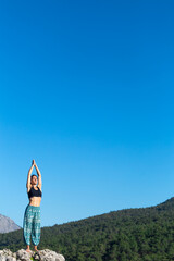 Fototapeta Girl practices yoga on top of the mountain.