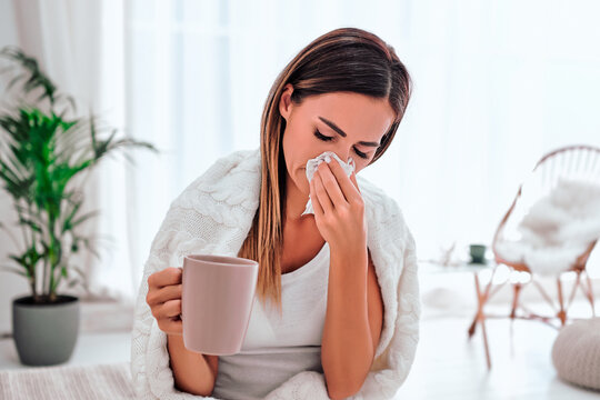 Pretty sick woman has runnning nose, rubs nose with handkerchief, drinks hot beverage, wrapped in warm blanket, has high temperature and cold.