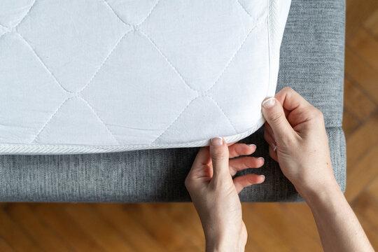 Woman hand wearing topper at orthopedic mattress