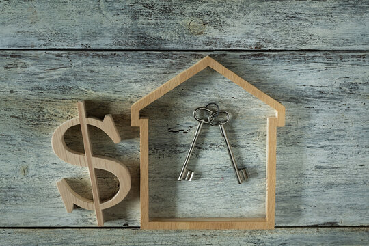 house modell with dollar sign and keys on wooden background
