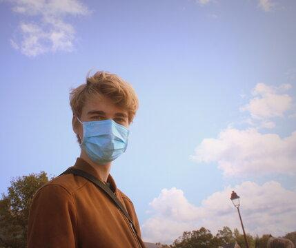 jeune homme portant un masque dans la rue