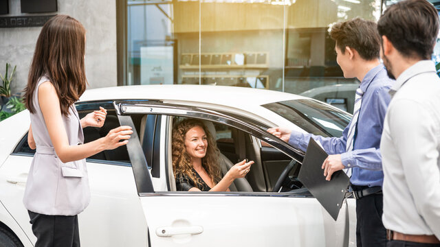 Car dealership. The Caucasian woman client in the new car is receiving the car key from the sales team before hand over. Auto Leasing Business.