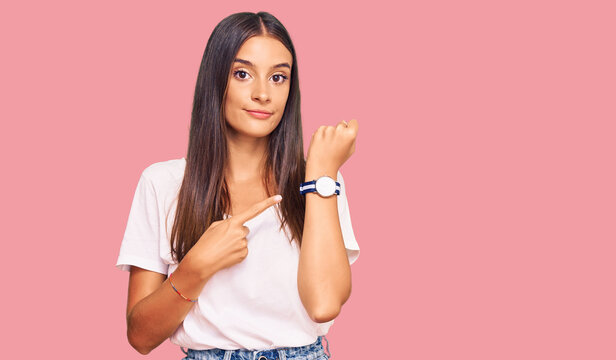 Young hispanic woman wearing casual white tshirt in hurry pointing to watch time, impatience, looking at the camera with relaxed expression