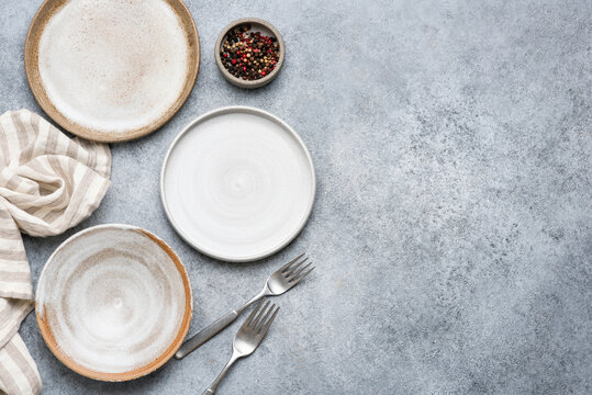 Table setting with trendy grey ceramic plates on grey concrete background. Top view